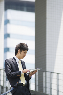 タブレットを操作するビジネスマンの素材 [FYI00941506]