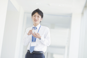 スマートフォンを操作するビジネスマンの素材 [FYI00941507]