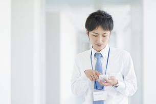 スマートフォンを操作するビジネスマンの素材 [FYI00941511]
