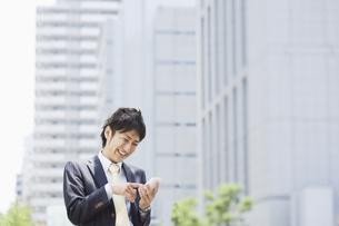 スマートフォンを操作するビジネスマンの素材 [FYI00941513]