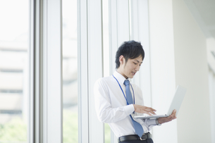 ノートパソコンを操作するビジネスマンの素材 [FYI00941514]