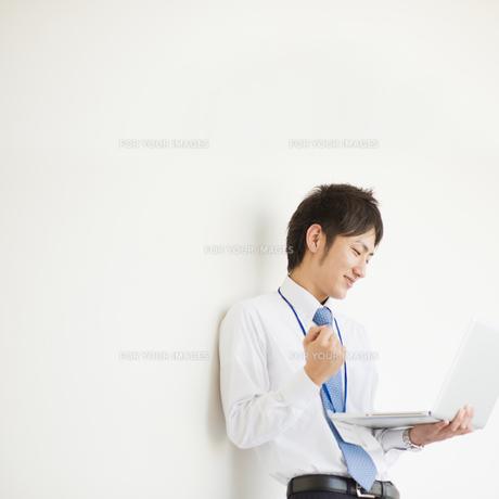 ノートパソコンを操作するビジネスマンの素材 [FYI00941524]