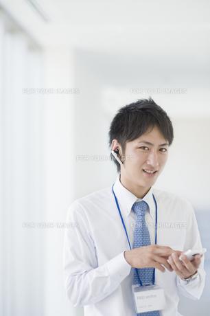 スマートフォンを操作するビジネスマンの素材 [FYI00941525]