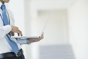 ノートパソコンを操作するビジネスマンの素材 [FYI00941529]
