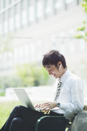 屋外でノートパソコンを操作するビジネスマンの素材 [FYI00941530]