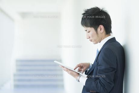 タブレットを操作するビジネスマンの素材 [FYI00941534]