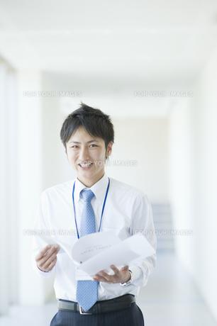 ファイルを持って微笑むビジネスマンの素材 [FYI00941535]