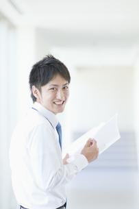 ファイルを持って微笑むビジネスマンの素材 [FYI00941544]
