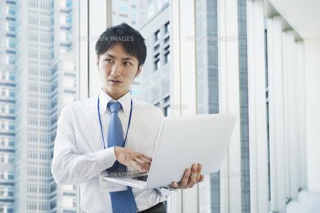 ノートパソコンを操作するビジネスマンの素材 [FYI00941547]