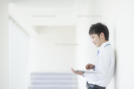 ノートパソコンを操作するビジネスマンの素材 [FYI00941553]