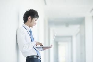 ノートパソコンを操作するビジネスマンの素材 [FYI00941554]