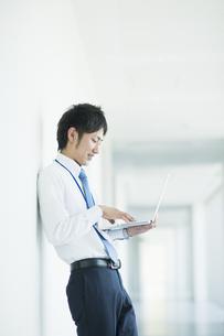 ノートパソコンを操作するビジネスマンの素材 [FYI00941556]