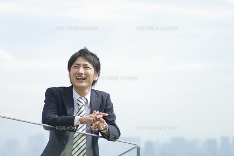 笑いながら遠くを見つめるビジネスマンの素材 [FYI00941558]