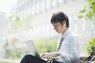 屋外でノートパソコンを操作するビジネスマンの素材 [FYI00941574]