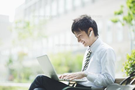 屋外でノートパソコンを操作するビジネスマンの素材 [FYI00941580]