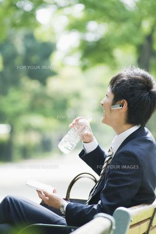 携帯電話で話しながら水を飲むビジネスマンの素材 [FYI00941605]