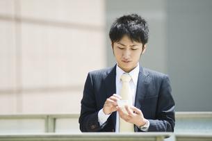 スマートフォンを操作するビジネスマンの素材 [FYI00941663]