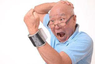 血圧を測定して驚くシニアの写真素材 [FYI00942380]