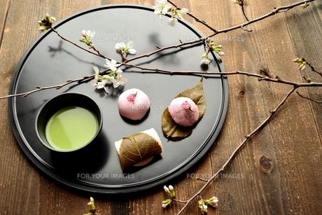 黒いおぼんの上の抹茶と桜の和菓子の写真素材 [FYI00942687]
