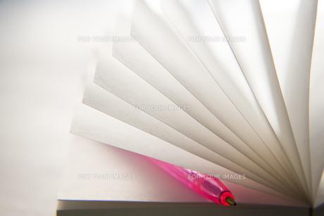 ノートの間に挟まったピンクのペンの素材 [FYI00943963]