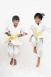 空手着姿で飛び上がる二人の子供の素材 [FYI00943968]