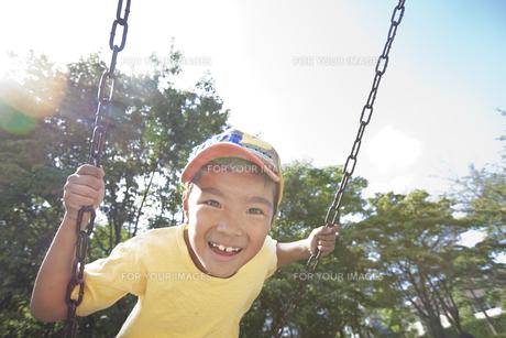 ぶらんこに乗る笑顔の男の子の素材 [FYI00943982]