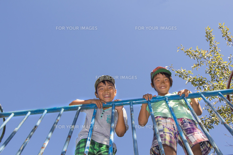 橋の欄干から顔をだす二人の少年の素材 [FYI00944024]