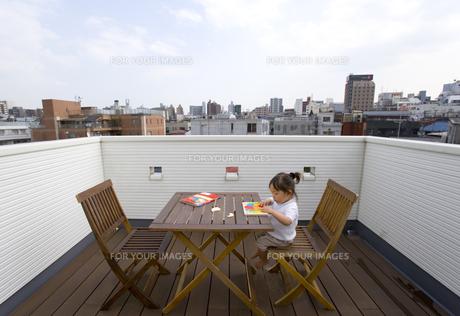 テラスの椅子に座って遊ぶ女の子の素材 [FYI00944031]