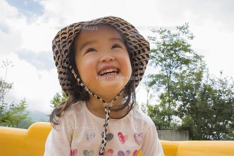 ベンチに坐って笑う女の子の素材 [FYI00944093]