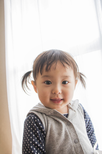 白いカーテンの前で笑う女の子の素材 [FYI00944156]