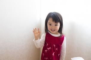 壁に手をあて笑う女の子の素材 [FYI00944163]