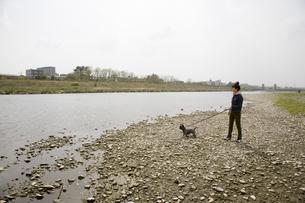 犬と河原を散歩をする20代女性の素材 [FYI00944187]