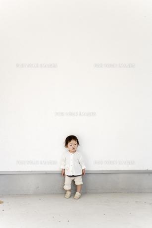 白い壁の前に立つ女の子の素材 [FYI00944219]