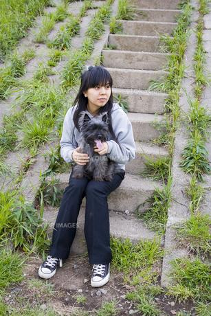 犬を抱いて階段に座る20代女性の素材 [FYI00944308]