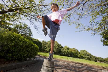 石の上から飛び降りる男の子の素材 [FYI00944322]