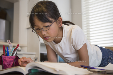 寝そべって勉強する少女の素材 [FYI00944370]