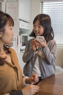 スマートフォンの操作を母親に聞く子供の素材 [FYI00944792]