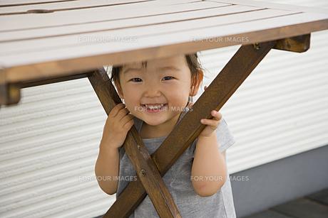 テーブルの下に座る女の子の素材 [FYI00944940]