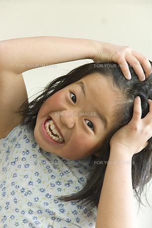 髪の毛を頭にあてる女の子の素材 [FYI00945001]