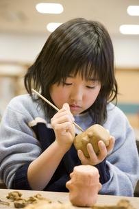 粘土をこねる小学生の女の子の素材 [FYI00945299]