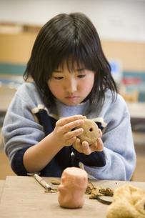 粘土をこねる小学生の女の子の素材 [FYI00945315]