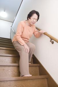 階段で膝を押さえるシニア女性の素材 [FYI00949408]