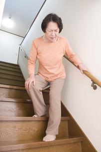 階段で膝を押さえるシニア女性の素材 [FYI00949547]