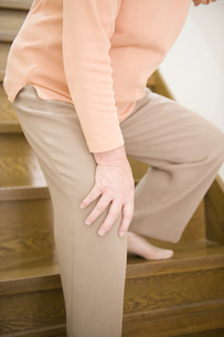 階段で膝を押さえるシニア女性の素材 [FYI00950569]
