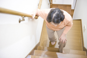 階段で膝を押さえるシニア女性の素材 [FYI00950571]