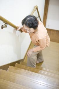 階段で膝を押さえるシニア女性の素材 [FYI00950609]