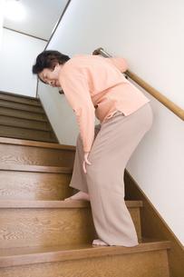 階段で膝を押さえるシニア女性の素材 [FYI00950641]