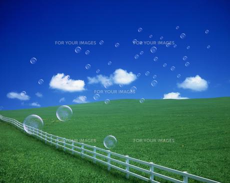 シャボン玉と白い柵と丘と雲の素材 [FYI00954438]