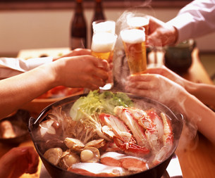 鍋料理と乾杯する人物の手元の素材 [FYI00960133]