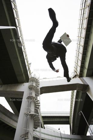 高速道路の高架下をジャンプするビジネスマンの素材 [FYI00961118]